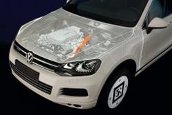 Frontansicht des Touareg Hybrid mit Motorblock und Hochspannungsleitung